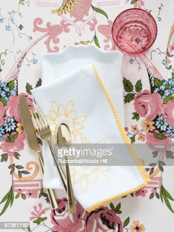 Plate with napkin and cutlery on floral tablecloth : Stock Photo