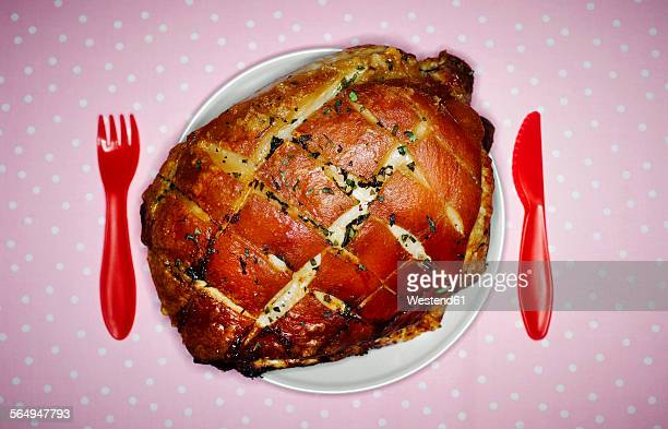 Plate with pork roast with crackling and red plastic cutlery on pink cloth