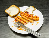 Plate with boiled sausages, ketchup and slices of butter while eating breakfast.