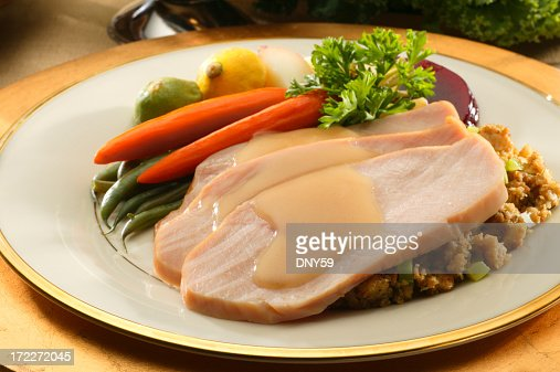 Plate with slices of turkey and side of cooked vegetables