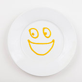 Plate with smiley face made of mustard
