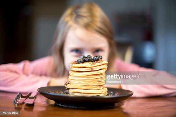 Plate with stack of pancakes with little girl in the background
