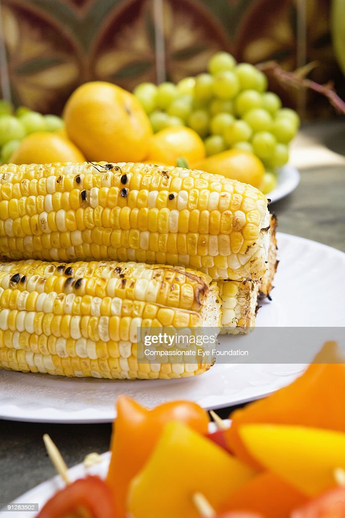 Plated corn on the cob on a table with other food