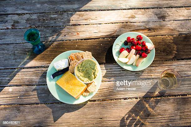 Plates of cheese and fruit on wooden table