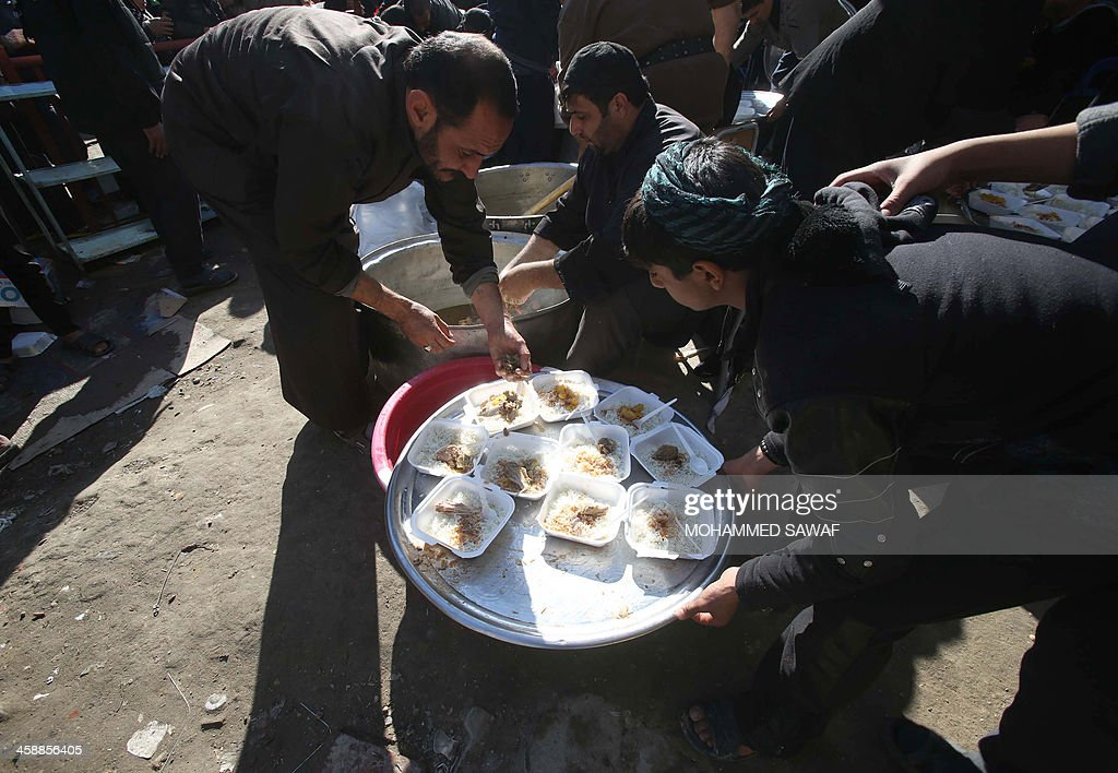 Plates of food are prepared which will be served to Shiite Muslim pilgrims visiting the central Iraqi shrine city of Karbala on December 22 as they...