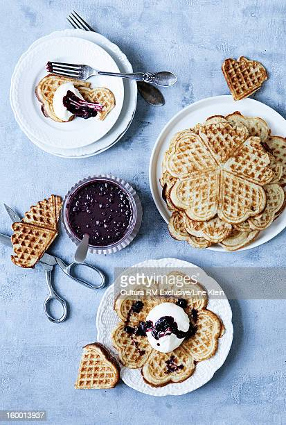 Plates of waffles with cream and jam