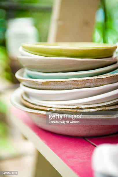 Plates stacked on shelf