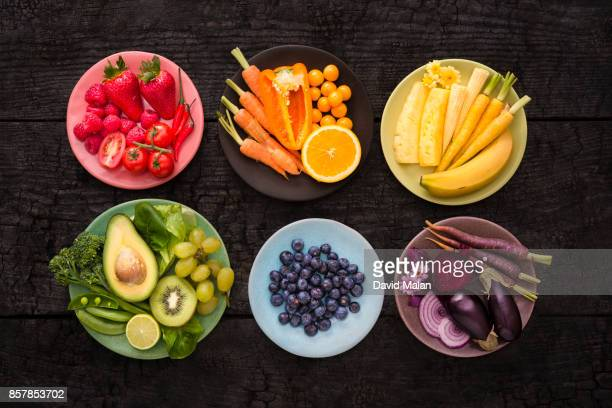 Plates with various coloured fruit & vegetables on a black surface.