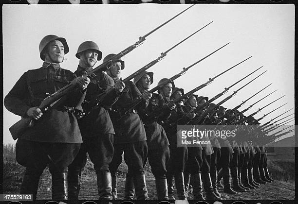 Platoon of Red Army soldiers in helmets and rifles tilted forwards circa 1940