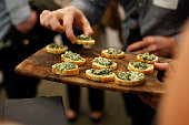 A platter of spinach and artichoke dip on tiny crackers is served by a waiter at an upscale event.