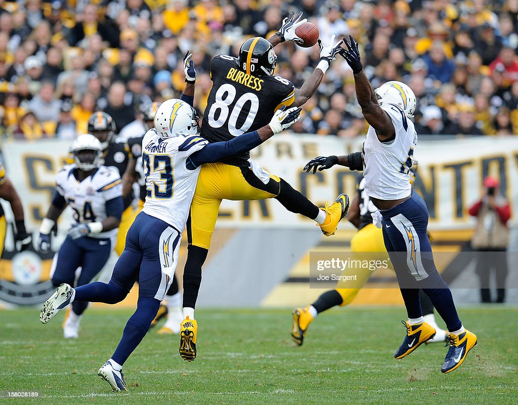 Plaxico Burress #80 of the Pittsburgh Steelers makes a catch between the defense of Quentin Jammer #23 and Takeo Spikes #51 of the San Diego Chargers on December 9, 2012 at Heinz Field in Pittsburgh, Pennsylvania.