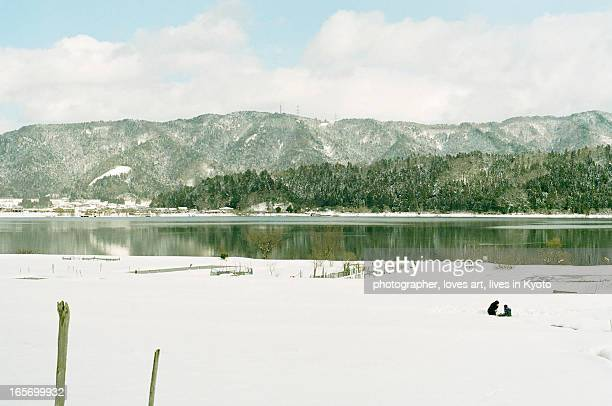 play in snowfield in front of a lake