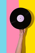 Female hand holding vinyl record over pink and blue and yellow background