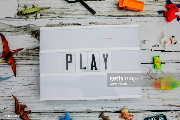 play word written in a light box.Toys around.Top view