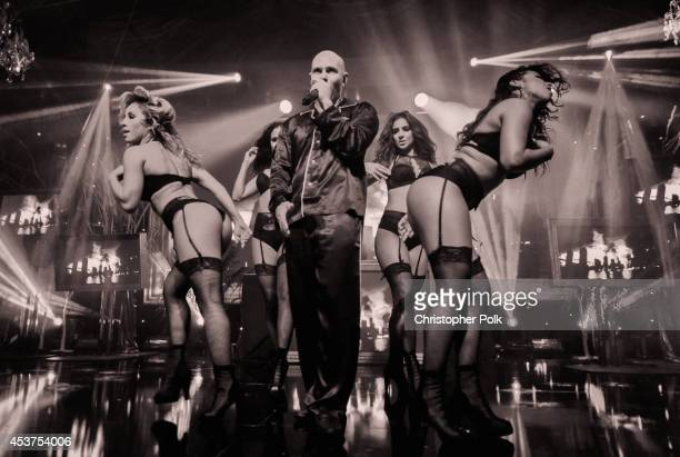 Playboy brand partner Pitbull performs onstage at the Annual Midsummer Night's Dream Party at the Playboy Mansion hosted by Hugh Hefner on August 16...