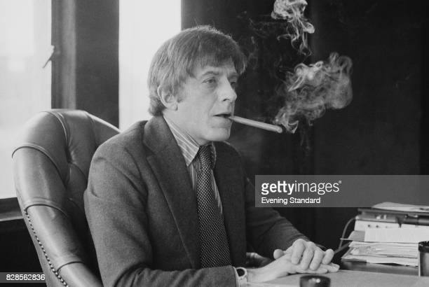 Playboy executive chief Victor Lownes smokes a cigar in his office UK 31st January 1975
