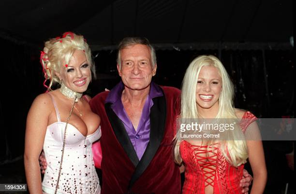 Playboy founder Hugh Hefner poses with two of his new girlfriends Tiffany Holliday left and Stephanie Heinrick February 9 2001 at the Playboy...