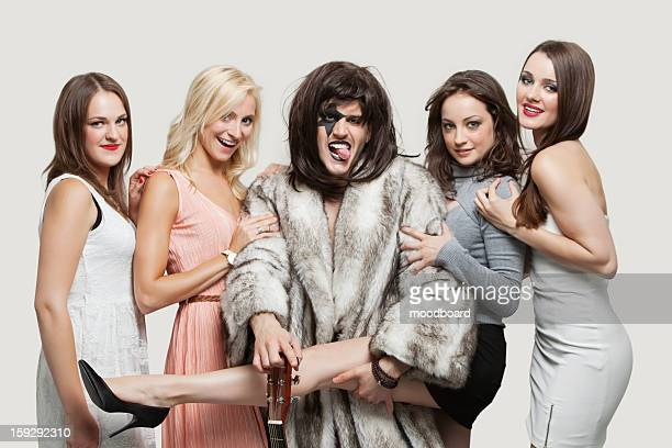 Playboy with beautiful women over gray background