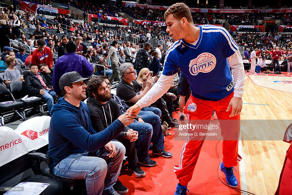 NFL player Aaron Rodgers speaks with Blake Griffin #32 of the Los Angeles Clippers before a game between the Milwaukee Bucks and Clippers at Staples Center on March 6, 2013 in Los Angeles, California.