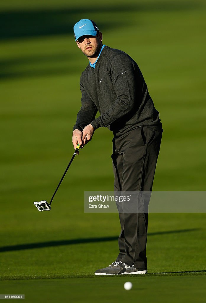 NFL player Aaron Rodgers watches a putt on the first green during the third round of the AT&T Pebble Beach National Pro-Am at Pebble Beach Golf Links on February 9, 2013 in Pebble Beach, California.