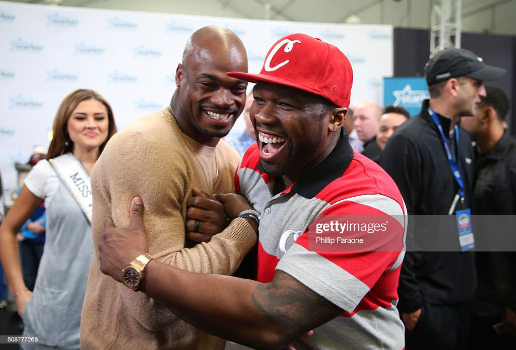 NFL player Adrian Peterson of the Minnesota Vikings (2nd from left) and rapper 50 Cent greet one another at the Starkey Hearing Foundation hearing mission during Super Bowl weekend 2016 at San Francisco State University on February 6, 2016 in San Francisco, California.