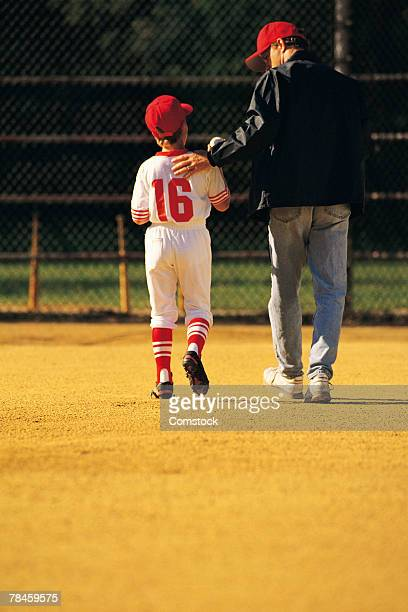 Player and coach leaving baseball field