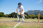Player batting at field against clear sky on sunny day