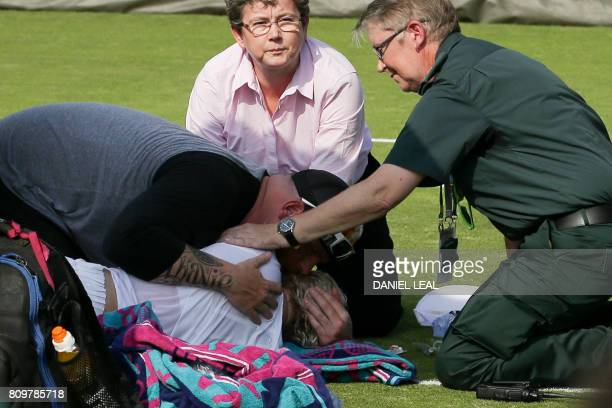 US player Bethanie MattekSands is comforted by her husband Justin Sands as she gets attention from medics on court after suffering an injury during...