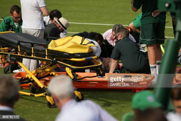 US player Bethanie MattekSands is helped by medics on court after suffering an injury during her women's singles second round match against Romania's...
