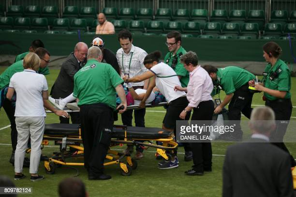 US player Bethanie MattekSands is lifted onto a trolley on a stretcher by medics on court after suffering an injury during her women's singles second...