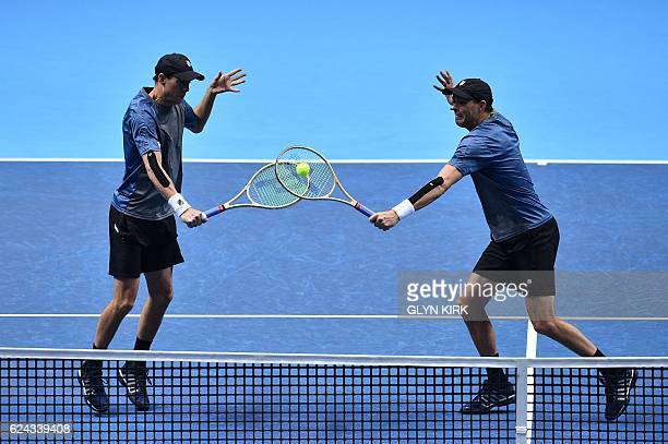 US player Bob Bryan and US player Mike Bryan go for the same ball against Finland's Henri Kontinen and his partner Australia's John Peers during...