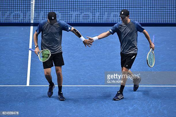 US player Bob Bryan and US player Mike Bryan touch hands between points against Finland's Henri Kontinen and his partner Australia's John Peers...