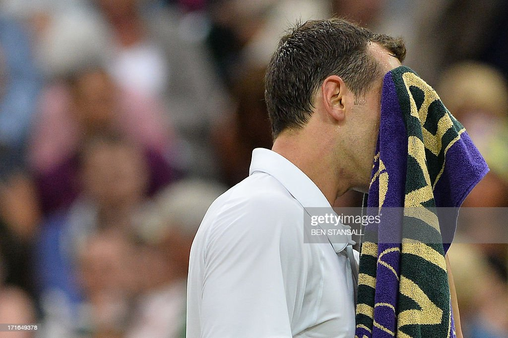 US player Bobby Reynolds uses his towel between points against Serbia's Novak Djokovic during their second round men's singles match on day four of the 2013 Wimbledon Championships tennis tournament at the All England Club in Wimbledon, southwest London, on June 27, 2013.
