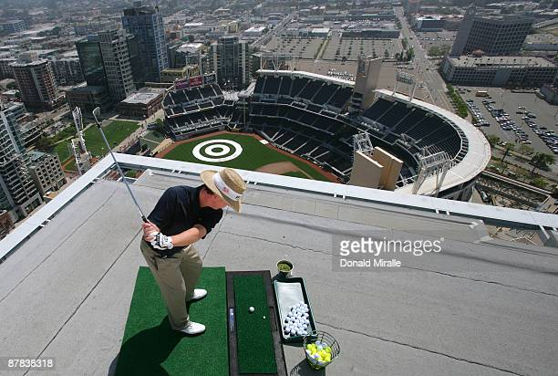 Player Briny Baird hits off the roof of the Omni Hotel attempting to land a golf ball on a bullseye planted in rightcenter field at PETCO Park during...