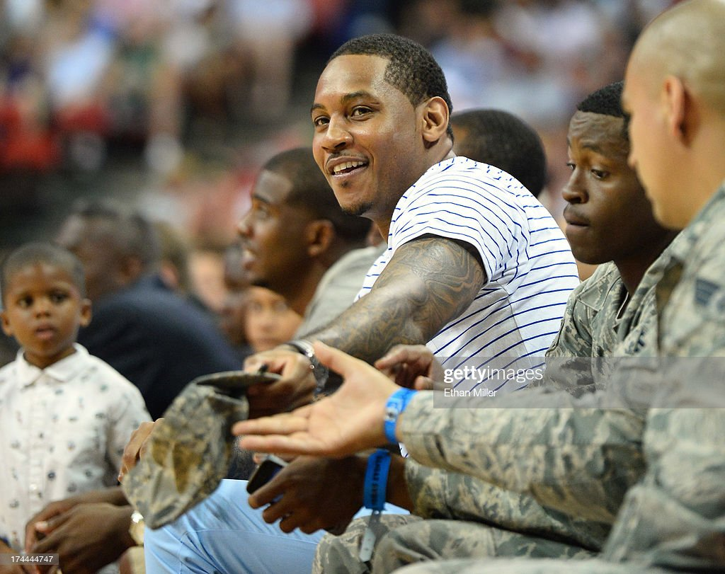 NBA player Carmelo Anthony of the New York Knicks signs autographs for members of the U.S. Air Force as he sits courtside during a USA Basketball showcase featuring the 2013 USA Basketball Men's National Team at the Thomas & Mack Center on July 25, 2013 in Las Vegas, Nevada.