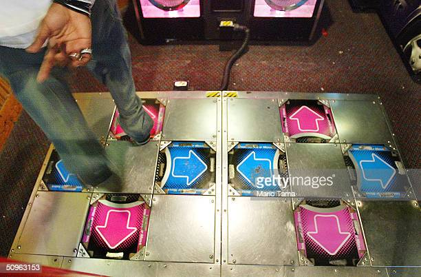 A player dances on the DDR or Dance Dance Revolution video game from Japan in a video game arcade June 15 2004 in New York City People across the...