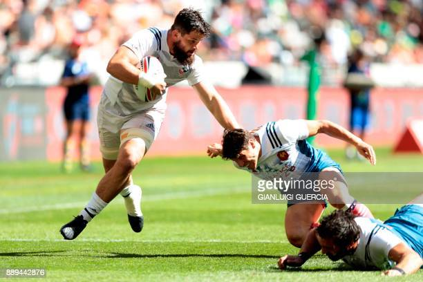 US player Danny Barrett hands off a French player after avoiding a tackle from Jean Baptiste Mazoue during their match on the second day of the World...