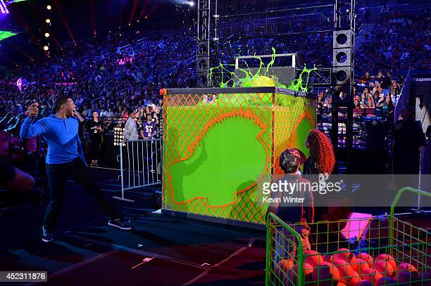 NFL player Earl Thomas gets dunked into slime onstage during Nickelodeon Kids' Choice Sports Awards 2014 at UCLA's Pauley Pavilion on July 17 2014 in...