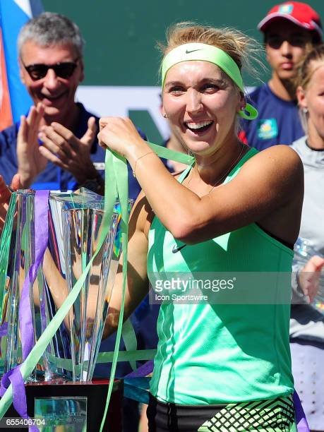 WTA player Elena Vesnina poses with the BNP Paribas Open winners trophy with streamers around her and the tropy after Vesnina defeated Svetlana...