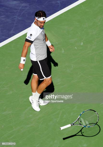 ATP player Fabio Fognini goes to retrieve hist racket after throwing it on the court during the third set of a match against JoWilfried Tsonga played...