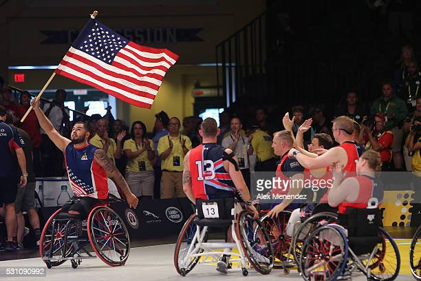 A player for the United States squad carries the American flag on the court during the Invictus Games Orlando 2016 Wheelchair Basketball Finals at...