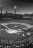 A player from the Boston Red Sox draws the bases loaded walk to score a run during an MLB game at Fenway Park circa 1955 in Boston Massachusetts