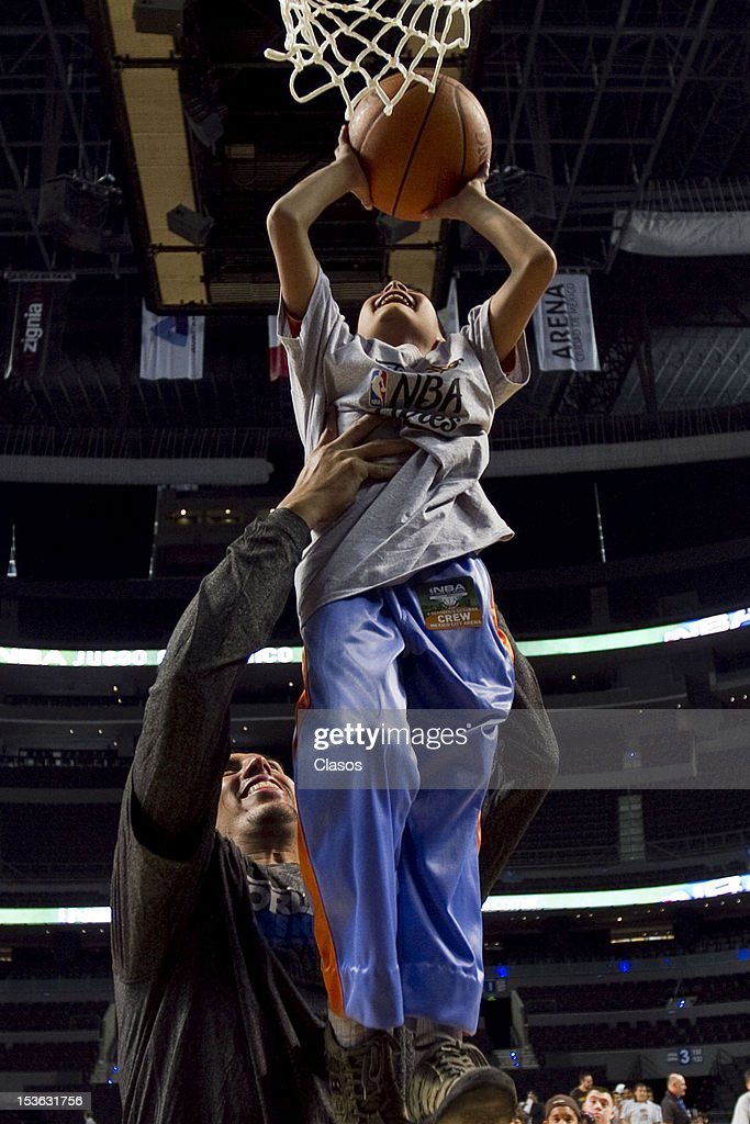 Player Gustavo Ayon plays with a kid during a training session of New Orleans Hornets and Orlando Magic with disabled people at Arena on October 06, 2012 in Mexico City, Mexico.
