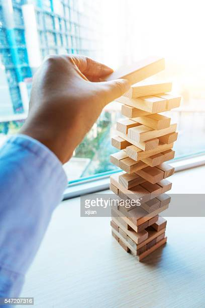 Player hand build Jenga tower
