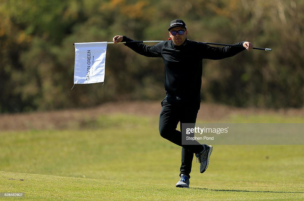 A player holds the flag on a green during the PGA Assistants Championship East Qualifier at Ipswich Golf Club on May 5, 2016 in Ipswich, England.