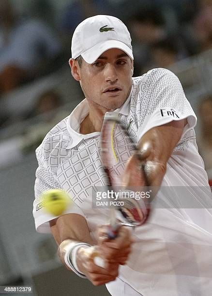 US player John Isner returns the ball to Spanish player David Ferrer during their men's singles third round tennis match of the Madrid Masters at the...
