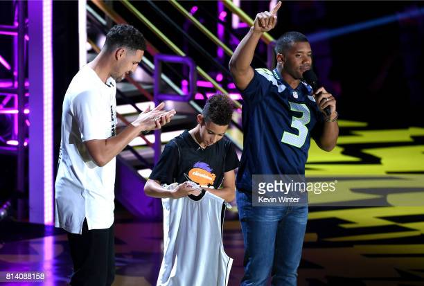 NBA player Klay Thompson athlete Austin Fernandes Cog Hill and host Russell Wilson participate in a competition onstage during Nickelodeon Kids'...