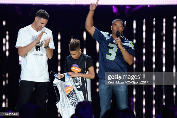 NBA player Klay Thompson Nate Simon and host Russell Wilson participate in a challenge during Nickelodeon Kids' Choice Sports Awards 2017 at Pauley...