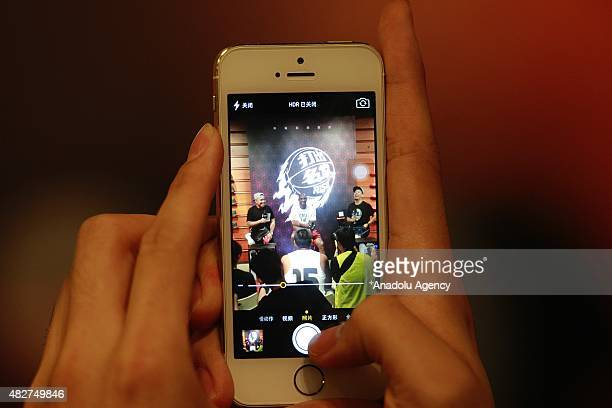 NBA player Kobe Bryant of the Los Angeles Lakers is seen on the screen of the mobile phone of a fan during a promotional event at a store in...