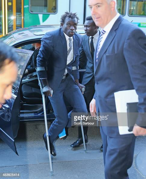 AFL player Majak Daw of the North Melbourne Kangaroos arrives on crutches to appear in Melbourne Magistrates Court on August 22 2014 in Melbourne...